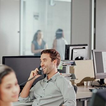 A Man Gray Shirt Talking On A Telephone - Cloud Analytics Platform - Infront